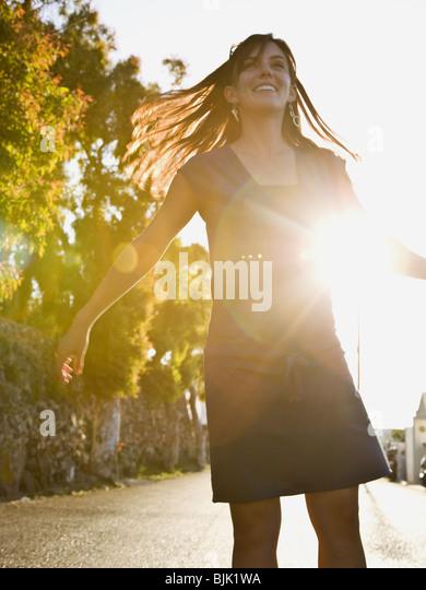 Frau stehen auf Straße in Silhouette mit Arme nach oben hinterleuchtet Stockbild