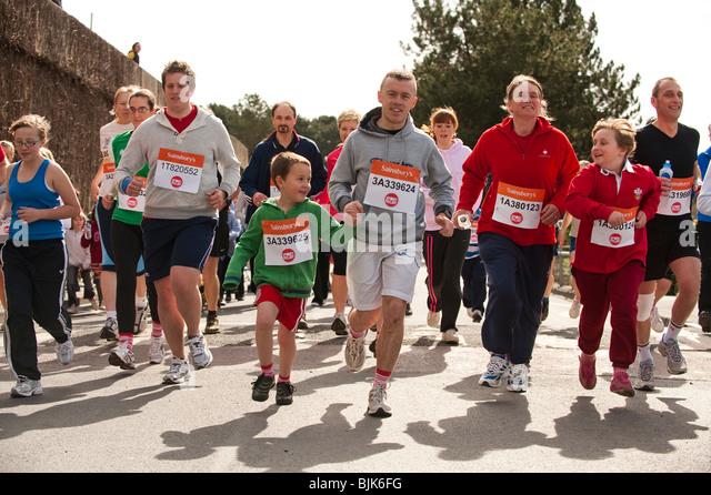 Menschen-Familien-Eltern und Kinder laufen in der Sporthilfe eine Meile gesponsert Nächstenliebe Volkslauf, Stockbild