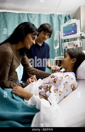 Mutter und Sohn im Gespräch mit Mädchen im Krankenhausbett Stockbild