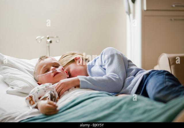 Mädchen mit Bruder am Krankenhausbett Verlegung Stockbild
