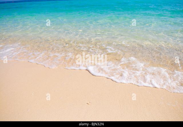 Tropischer Strand mit weißen Korallen Sand und ruhigem wave Stockbild
