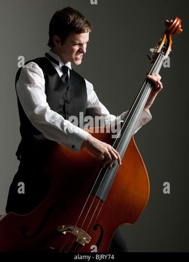 Junger Mann Christbaumkugel Bass zupfen Stockbild