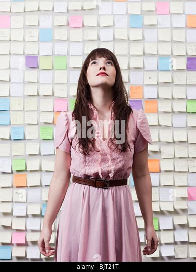 Porträt der Frau in Raum mit Wänden, die mit Klebstoff Notizen bedeckt Stockbild