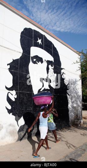 Angolaner gehen vorbei an Che Guevara Wandbild im Zentrum von Sumbe. Sumbe, Provinz Kwanza Sul, Angola. Afrika. Stockbild
