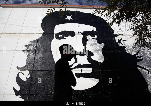 Angolaner gehen vorbei an Che Guevara Wandbild im Zentrum von Sumbe. Sumbe, Provinz Kwanza Sul, Angola. Afrika Stockbild
