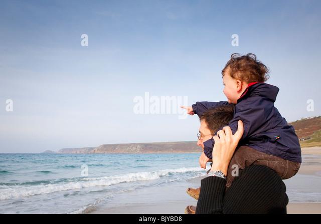 Mann mit Kind auf Schultern schauen um zu sehen. Kind zeigt. Stockbild