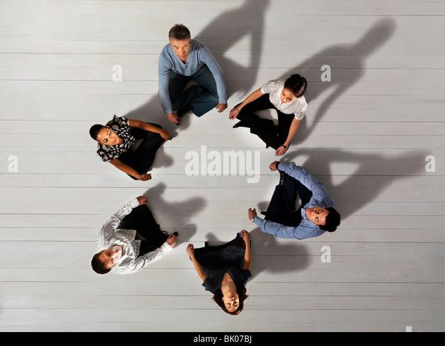 Business-Männer und Frauen sitzen im Kreis Stockbild