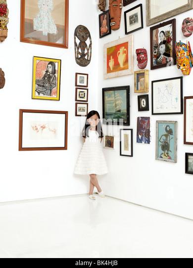 Mädchen stehen in der Ecke, umgeben von Kunstwerken Stockbild