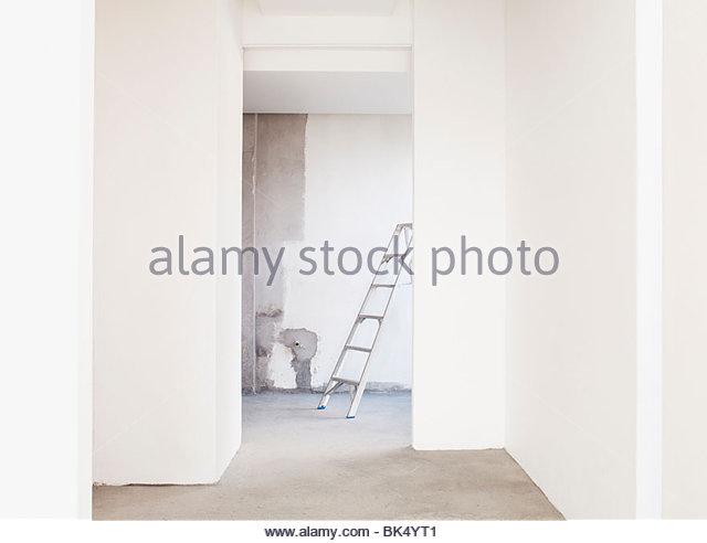 Leiter und frisch gestrichene Wände in leeren Haus Stockbild