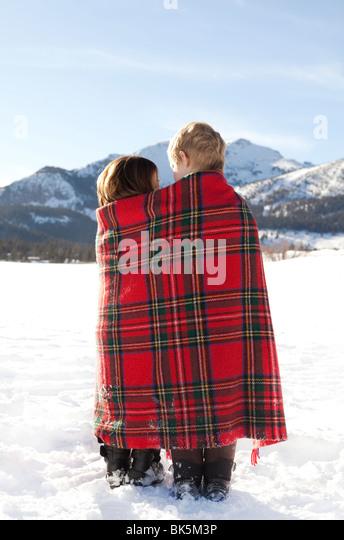 Jungen und Mädchen in rot karierten Decke im Schnee gewickelt Stockbild