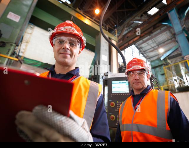 Stahl-Ingenieure im Werk mit Zwischenablage Stockbild