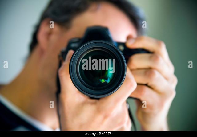 Mann, der ein Bild auf den Betrachter Stockbild
