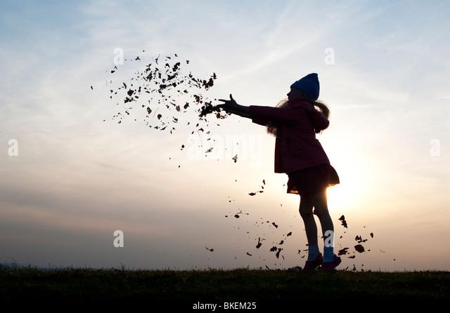 Junges Mädchen Spaß Blätter zu werfen. Silhouette Stockbild