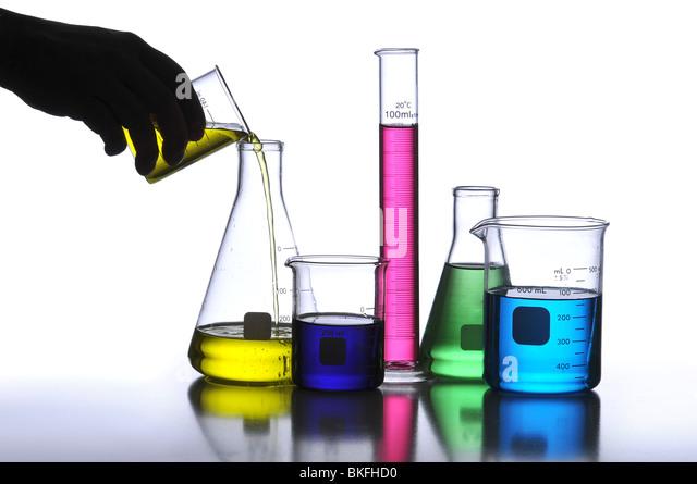 Labor Glaswaren mit verschiedenen farbigen Flüssigkeiten vor einem neutralen Hintergrund Stockbild