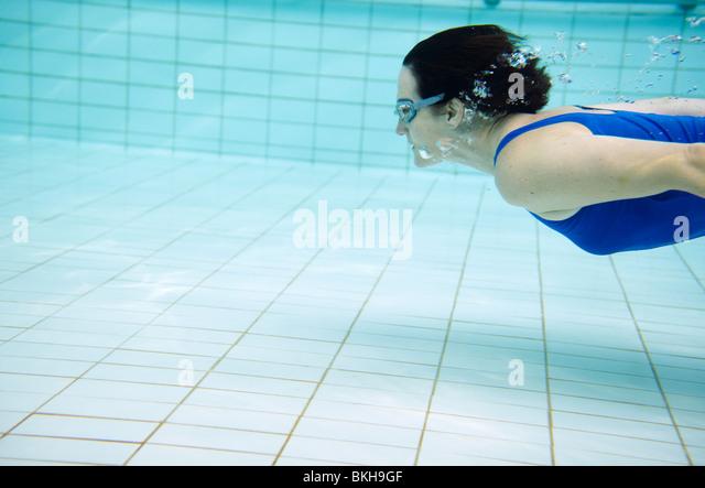 Frau in blauen Badeanzug schwimmen unter Wasser im pool Stockbild