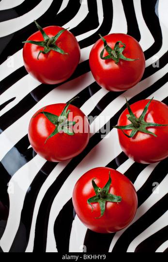 5 Tomaten auf gestreiften Teller Stockbild