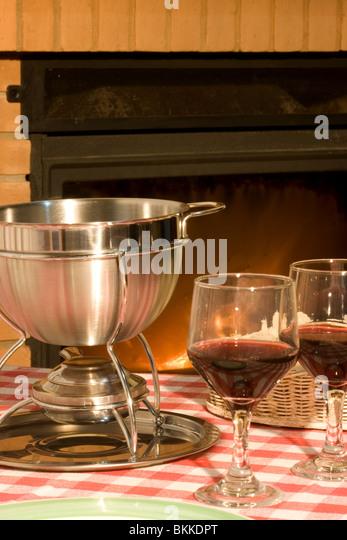 Käse-Fondue und Wein vor dem Kamin Stockbild