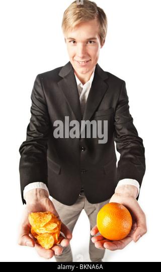 Lächelnder junge Mann bietet eine Auswahl zwischen gesunden und ungesunden Essen Stockbild