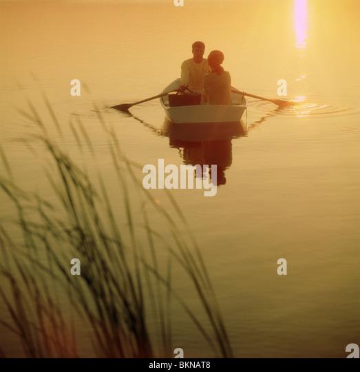 Paar auf einem Ruderboot während des Sonnenuntergangs Stockbild