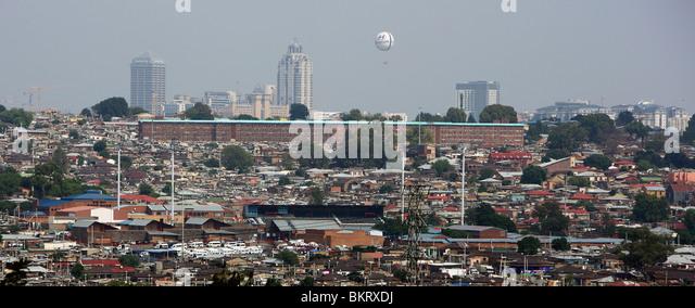 Schauen Sie über Township Alexandra auf Luxus Stadtteil Sandton City im Hintergrund mit seinen Hotels und Einkaufszentren Stockbild