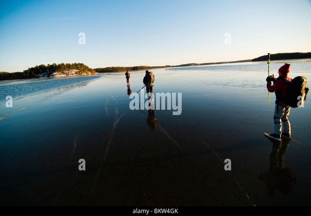 Drei Menschen Eislaufen auf dem zugefrorenen See Stockbild