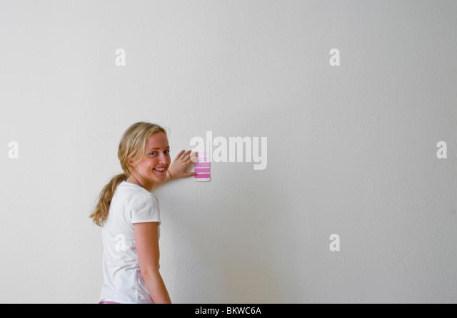 Frau stehend gegen Wand Farbe auswählen Stockbild