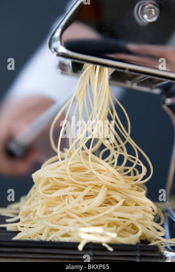 Haufen von frische Tagliolini kommen aus einer Nudelmaschine mit der Hand drehen am Griff Stockbild