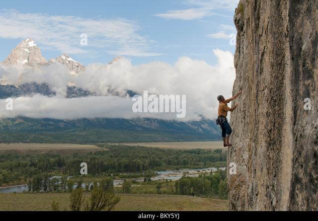 Ein Mann Klettern eine Felswand unterhalb der Tetons, Black Tail Butte, Jackson, Wyoming. Stockbild