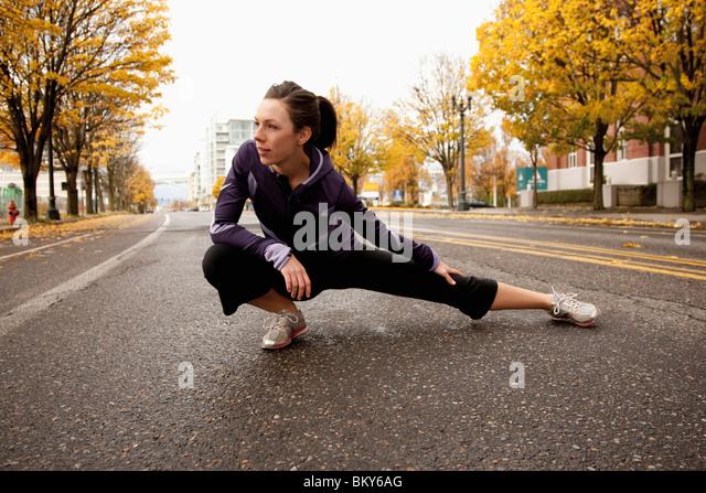Eine sportliche Frau in eine lila Jacke erstreckt sich entlang einer verlassenen Straße in Portland, Oregon. Stockbild