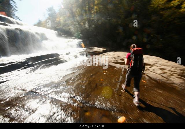 Bewegungsunschärfe der Frau zu Fuß am Fuße des Wasserfalls. Stockbild