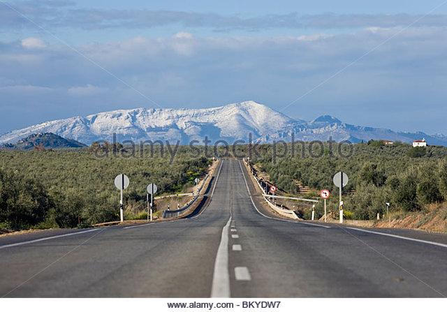 Landstraße E-902 aus Ubeda, Jaen mit Schnee bedeckt die Berge im Hintergrund, Provinz Jaén, Andalusien, Stockbild
