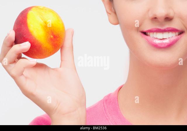 Nahaufnahme einer Frau mit einem Pfirsich Stockbild