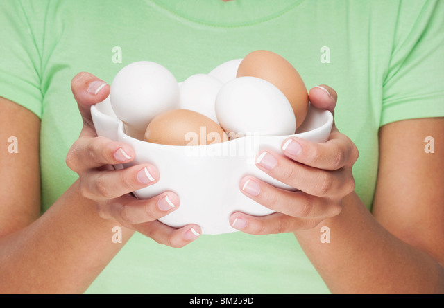 Nahaufnahme einer Frau mit einer Schüssel Eier Stockbild
