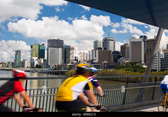 Radfahrer auf der Geschäfts-oder Firmenwert-Brücke mit der Stadt Skyline im Hintergrund. South Bank, Brisbane, Stockbild