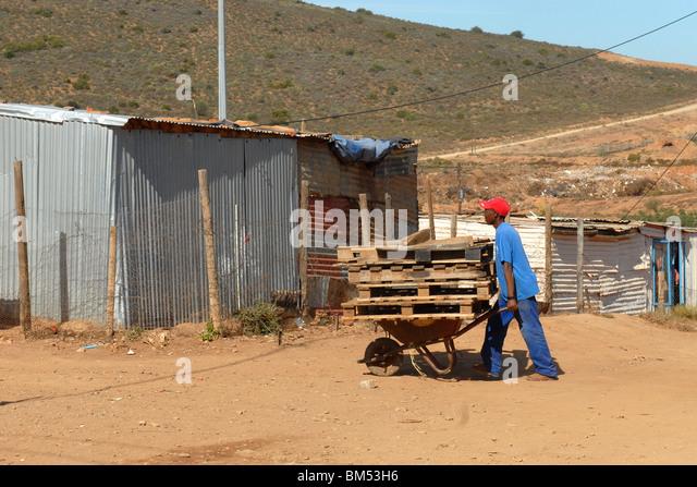 Mann bei der Arbeit mit seiner Schubkarre im township Stockbild