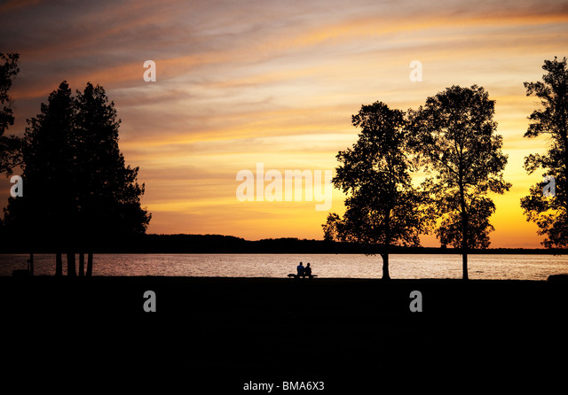 Älteres Ehepaar, Silhouette, sitzen auf einer Bank See bei Sonnenuntergang Stockbild