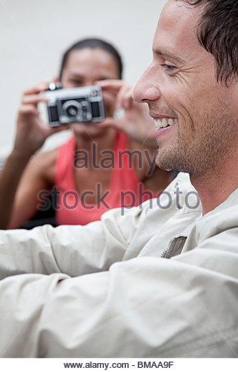 Junge Frau nehmen Foto des Mannes im Cabrio Stockbild