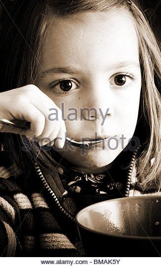 Vier Jahre altes Kind Essen aus einer Schüssel mit dem Löffel Stockbild