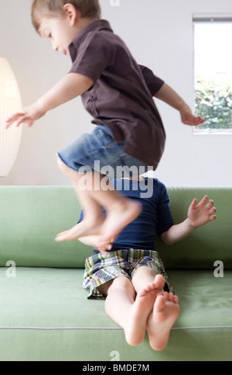 Junge springt über seinen Bruder auf sofa Stockbild
