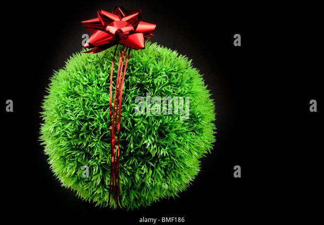 Grünen Rasen Ball mit roter Schleife und Band drüber, ein Geschenk für die Erde Stockbild