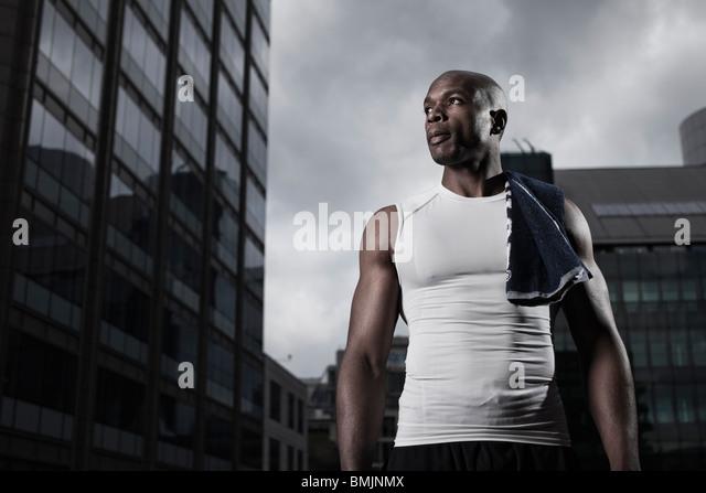 Passen Sie Mann trägt Sportbekleidung hintergründig durch moderne Stadtgebäude Stockbild