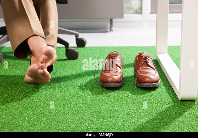 Entspannte Füße auf einem grünen Büroteppich - Stock-Bilder