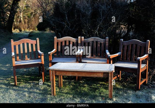 Eis Frost bedeckt Gartenmöbel Holzsitz Bank Winter kalt Hecke Sitz Stühle Tisch Licht Sonnenaufgang Stockbild