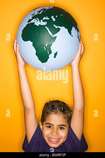 Ein Junge hält einen Globus Stockbild
