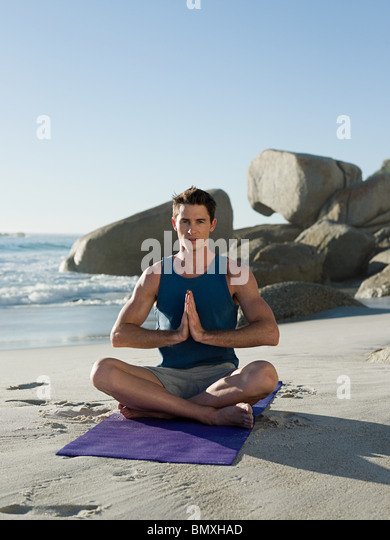 Junger Mann beim Yoga am Strand Stockbild