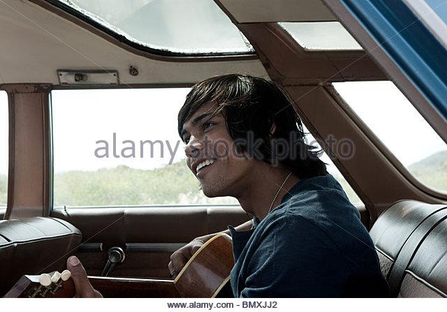 Junger Mann in Auto Gitarre spielen Stockbild