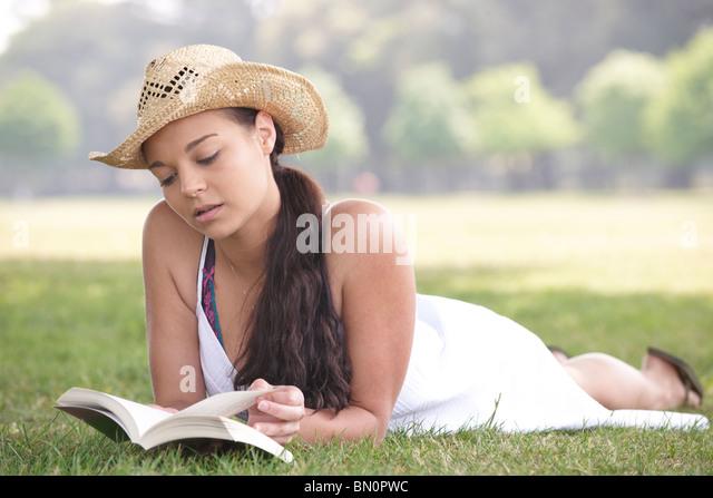 junge attraktive Mädchen beim Lesen eines Buches auf dem Rasen liegend Stockbild
