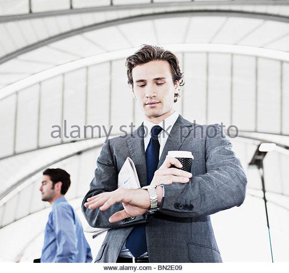 Geschäftsmann mit Kaffee Uhrzeit kontrollieren Stockbild
