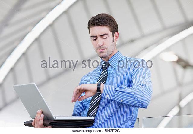 Geschäftsmann mit Laptop überprüfen der Zeit Stockbild