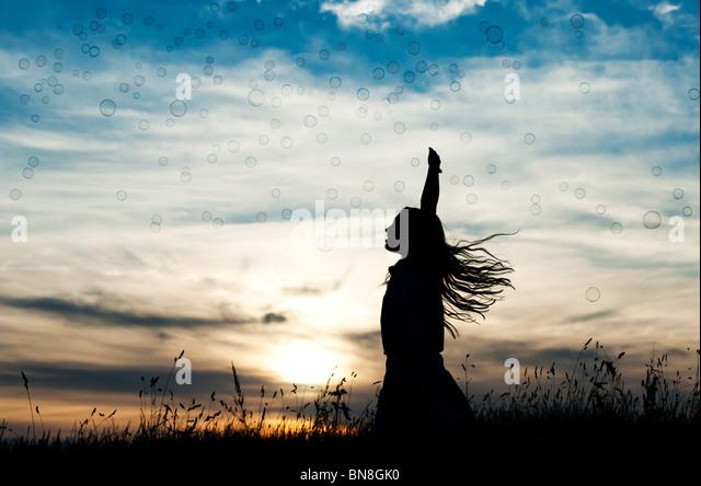 Young Girl energetisch Spaß springen und fangen Luftblasen bei Sonnenuntergang. Silhouette Stockbild